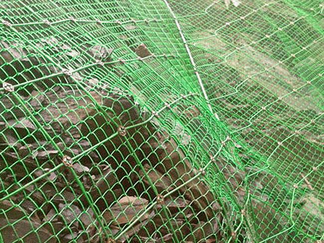 主动防护系统是以钢丝绳网为主的各类柔性网覆盖包裹在所需防护斜坡或岩石上,以限制坡面岩石土体的风化剥落或破坏以及为岩崩塌(加固作用),或将落石控制于一定范围内运动(围护作用)。 材质: 钢丝绳网、普通钢丝格栅(常称铁丝格栅)和TECCO高强度钢丝格栅。 构造: 前两者通过钢丝绳锚杆和/或支撑绳固定方式,后者通过钢筋(可施加预应力)和/或钢丝绳锚杆(有边沿支撑绳时采用)、专用锚垫板以及必要时的边沿支撑绳等固定方式 。 产品特性: 作用原理上类似于喷锚和土钉墙等面层护坡体系,但因其柔性特征能使系统将局部集中荷载